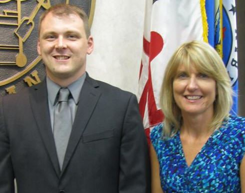 Jason M. Bennett, Director of Finance, standing with Pamela S. Diaz, Assistant Director of Finance.
